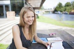 Jeune étudiant en dehors de la lecture, prenant des notes et le sourire Photos stock