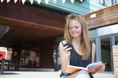 Jeune étudiant en dehors de la lecture, prenant des notes et le sourire Image stock