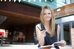 Jeune étudiant en dehors de la lecture, prenant des notes et le sourire Photo libre de droits