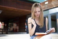 Jeune étudiant en dehors de la lecture, prenant des notes et le sourire Images stock