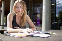 Jeune étudiant en dehors de livre et du sourire de lecture Images libres de droits