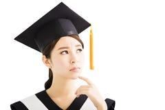 Jeune étudiant féminin d'obtention du diplôme recherchant et pensant photo stock
