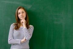 Jeune étudiant féminin de sourire sûr de lycée se tenant devant le tableau dans la salle de classe image stock