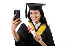 Jeune étudiant gradué féminin prenant le selfie Photo stock