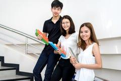 Jeune étudiant Group Holding Book et sourire d'ordinateur portable Photo libre de droits