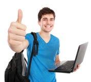 Jeune étudiant masculin avec l'ordinateur portable montrant le pouce  Photo stock
