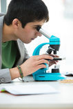 Jeune étudiant masculin bel scrutant par le microscope photo stock