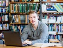 Jeune étudiant masculin dactylographiant sur l'ordinateur portable à la bibliothèque universitaire photos stock