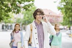 Jeune étudiant masculin de sourire à l'aide du téléphone portable avec des amis à l'arrière-plan sur la rue Photographie stock libre de droits