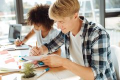 Jeune étudiant masculin positif étudiant avec son groupmate Image stock