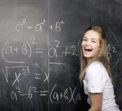 Jeune étudiant mignon près de tableau noir avec le stylo de calculatrice de livre de copie, l'espace de copie Images stock