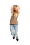 Jeune étudiant occasionnel sautant montrant des pouces  Image stock
