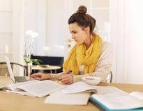 Jeune étudiant occupé avec l'étude Photo stock