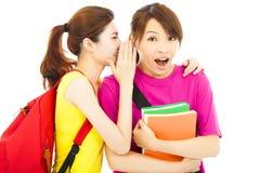 Jeune étudiant parlant à son ami avec l'expression étonnée Photographie stock libre de droits
