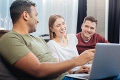 Jeune étudiant positif riant tout en regardant l'écran d'un ordinateur portable Image stock