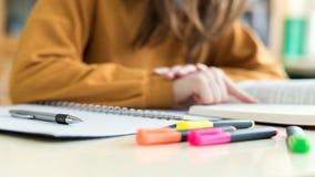Jeune étudiant universitaire féminin méconnaissable dans la classe, lisant le manuel Étudiant focalisé dans la salle de classe images libres de droits