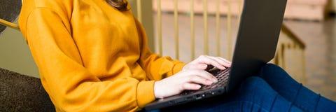 Jeune étudiant universitaire féminin s'asseyant sur des escaliers à l'école, écrivant l'essai sur son ordinateur portable Éducati photos libres de droits