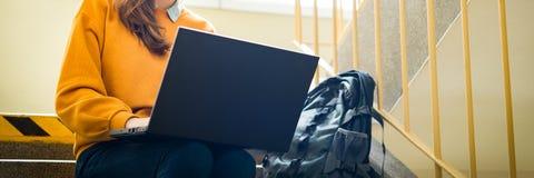 Jeune étudiant universitaire féminin s'asseyant sur des escaliers à l'école, écrivant l'essai sur son ordinateur portable réserve image stock