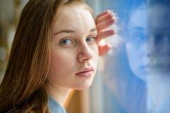 Jeune étudiant universitaire féminin seul déprimé se tenant prêt une fenêtre à son école, regardant l'appareil-photo Concept de i photo libre de droits