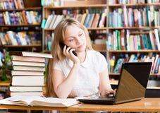 Jeune étudiante dans la bibliothèque dactylographiant sur l'ordinateur portable et parlant dessus Photos libres de droits