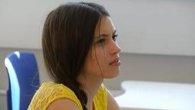Jeune étudiante dans la salle de classe écoutant un conférencier Photographie stock