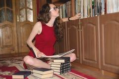 Jeune étudiante essayant de trouver des informations dans la bibliothèque Photos stock