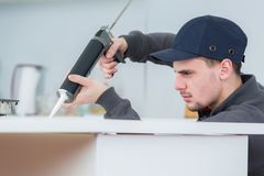 Jeune évier focalisé de cachetage de technicien dans la cuisine de clients photo stock