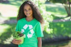 Jeune activiste environnemental souriant à l'appareil-photo tenant une usine mise en pot photos stock