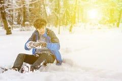 Jeune adolescent de garçon s'asseyant sur l'au sol de neige en parc f d'hiver photographie stock