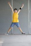 Jeune adolescent portant le T-shirt jaune et sauter photographie stock libre de droits