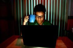 Jeune adolescent tenant une tasse de café devant un ordinateur portable Photos stock