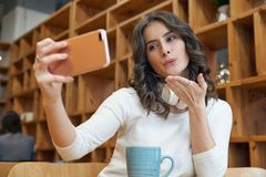 Jeune adolescente attirante de fille avec de longs cheveux bouclés envoyant un ki photos libres de droits