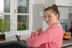 Jeune adolescente avec le chandail rose mangeant du maïs éclaté à la maison photo stock
