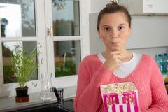 Jeune adolescente avec le chandail rose mangeant du maïs éclaté à la maison photos stock
