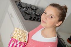 Jeune adolescente avec le chandail rose mangeant du maïs éclaté à la maison images stock