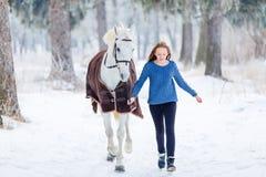Jeune adolescente avec le cheval blanc en parc d'hiver Photo stock