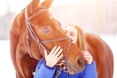 Jeune adolescente avec son cheval en parc d'hiver Photographie stock libre de droits