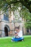 Jeune adolescente causant par le smartphone en Glasgow University Photos stock