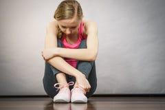 Jeune adolescente déprimée triste s'asseyant par le mur Photos stock