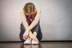 Jeune adolescente déprimée triste s'asseyant par le mur Photo stock