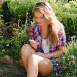 Jeune adolescente heureuse à l'aide du téléphone portable Photographie stock libre de droits