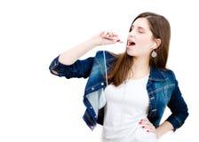Jeune adolescente heureuse chantant avec le lecteur de musique sur le copyspace blanc de fond Photographie stock libre de droits