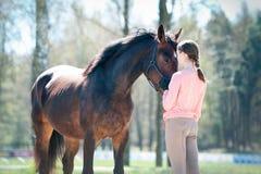 Jeune adolescente se tenant avec son cheval brun préféré image libre de droits