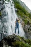 Jeune adolescente se tenant sur la grande cascade proche en pierre photos stock