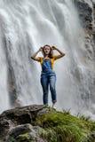 Jeune adolescente se tenant sur la grande cascade proche en pierre photos libres de droits