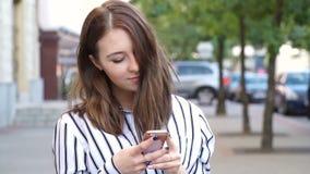 Jeune adolescente textotant dehors au téléphone au coucher du soleil, souriant clips vidéos