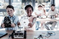 Jeune adorable montrant leurs machines robotiques Photo libre de droits