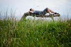 Jeune adulte détendant paisiblement en nature Image stock