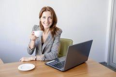 Jeune adulte féminin mignon travaillant sur l'ordinateur portable au bureau à côté de la tasse de café photographie stock