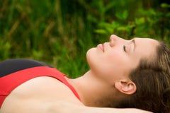Jeune adulte folâtre se reposant dans l'herbe Image stock